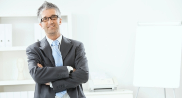 Portrait of gray haired executive businessman at office, smiling.