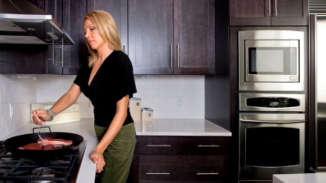 blonde woman cooking red meat